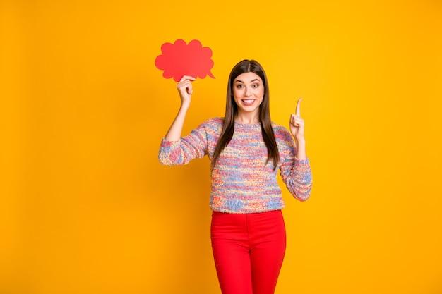 Omg het is ongelooflijk! verbaasd meisje houd rode papercard zeepbel denk gedachten krijgen idee wijsvinger omhoog beslissen beslissingen kiezen keuze dragen trui geïsoleerde gele kleur