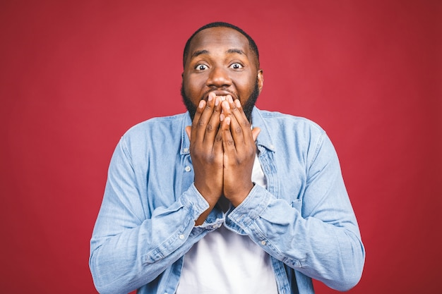 Omg. het portret van de grappige jonge zwarte mens met wijd geopende mond en kaak viel, zijn gehele blik die schok uitdrukt die over rood wordt geïsoleerd.