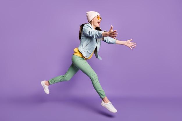 Omg ik heb je al tijden niet meer gezien. volledige lengte profiel kant foto opgewonden meisje zie vriend springen rennen wil knuffel omhelzing draag groen gele broek hoofddeksel zonnebril geïsoleerde paarse kleur achtergrond
