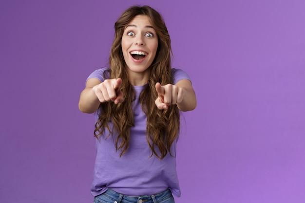 Omg jij bent het. verrast meisje fan juichen vreugdevol staren camera knallende ogen wijzende vingers naar voren verbaasde uitdrukkelijke bewondering zie superster wil handtekening ontvangen staan paarse achtergrond