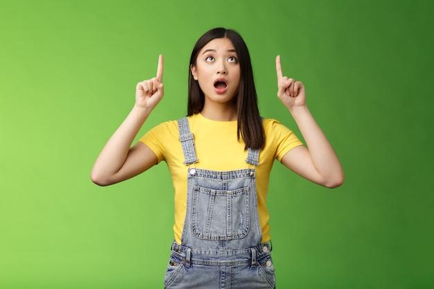 Omg kijk schokkende prijsdaling. verbijsterd sprakeloos verbaasd aziatisch meisje laat de kaak vallen, vraagt zich af wat er boven gebeurt, wijst onder de indruk, starend verbaasd staan groene achtergrond