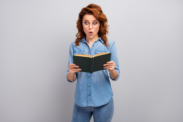 Omg ongelooflijk! verbaasde mooie vrouw leest een papieren boek onder de indruk van het onverwachte einde van het verhaal ziet er goed uit draag stijlvolle kleding geïsoleerd over een grijze kleurmuur