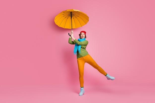 Omg parasol vlieg weg! foto op ware grootte van een verbaasd meisje, probeer haar heldere paraplu te vangen, voel angst, staar, kijk stomheid, draag een broek, rode hoofddeksels, schoenen, trui, geïsoleerd over een roze kleurmuur