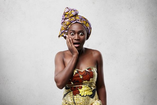 Omg! verrast of doodsbang afrikaanse vrouw die hand op wang vasthoudt en er geschokt uitziet, met uitgestoken ogen en wijd open mond