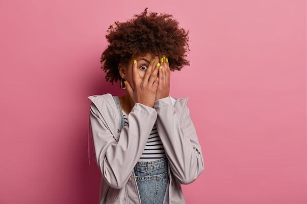 Omg, wat beangstigend! angstige vrouw met krullend haar gluurt door vingers, verbergt gezicht met handpalmen, kijkt met een bange uitdrukking, wil niet iets vreselijks zien, draagt grijze jas geïsoleerd op roze muur