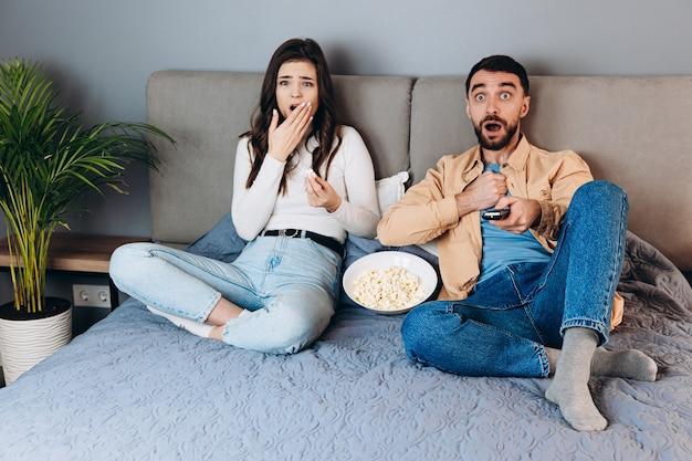 Omg wat is het. lief stel heeft in quarantaine vrije tijd film kijken onder de indruk verrast onverwachte thrillerfilm eindigend met popcorn