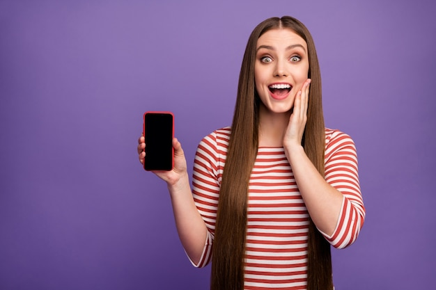 Omg ziet er nieuw apparaat uit! verbaasd verrast meisje houdt mobiel aanwezig ongelooflijke advertentie promotie onder de indruk schreeuw wow omg draag trui geïsoleerd over paarse kleur muur