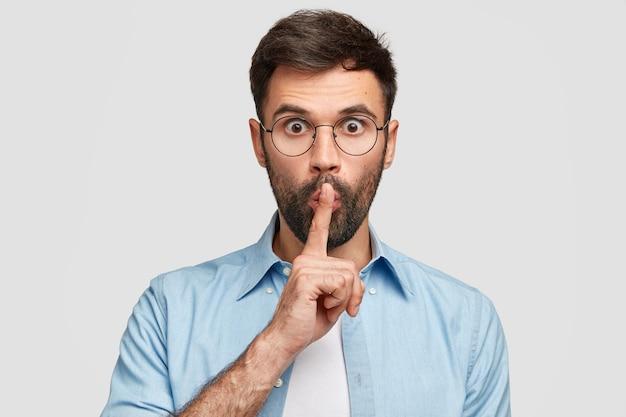 Omg, zwijg! verbaasde jonge man raakt lippen met wijsvinger, staart, maakt stil gebaar, bang dat iemand zijn geheim zal vertellen, heeft dikke haren, geïsoleerd over witte muur