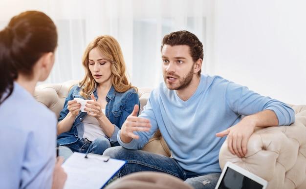 Omgaan met problemen. depressief ongelukkig jong stel dat een afspraak heeft met een psycholoog en haar hun problemen beschrijft terwijl ze op zoek zijn naar een oplossing