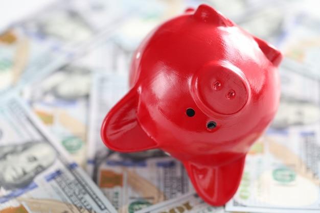 Omgekeerd rood spaarvarken ligt op honderd-dollarbiljetten geaccumuleerd spaarinflatieconcept