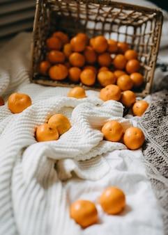 Omgekeerde mand vol sinaasappels die op dekens op bed liggen.