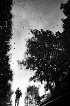 Omgekeerde reflectie in een plas van een voorbijganger die op straat loopt