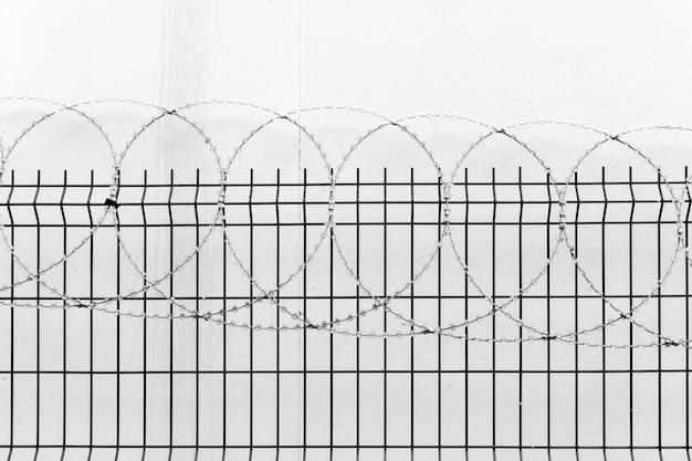 Omheining met prikkeldraad op witte muur
