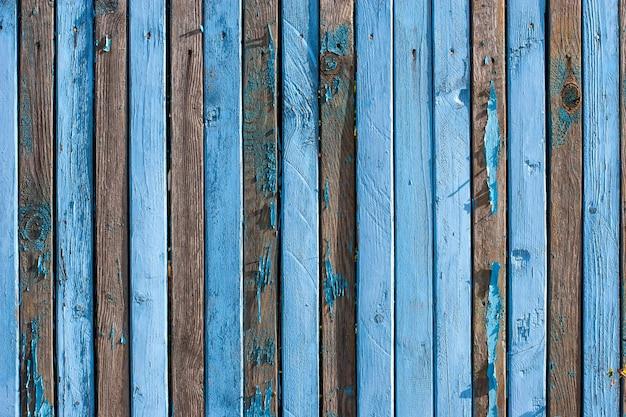 Omheining van smalle oude blauwe planken met rij spijkers