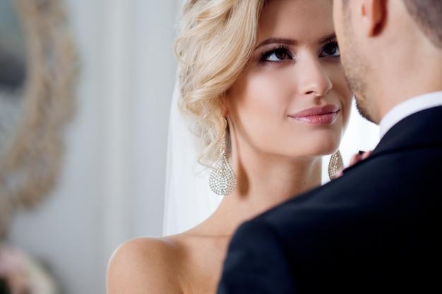 Omhels op trouwdag. mooie bruid die bruidegom in de hals omhelst