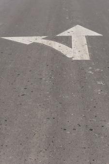 Omhoog en links wijzende pijlen op asfalt