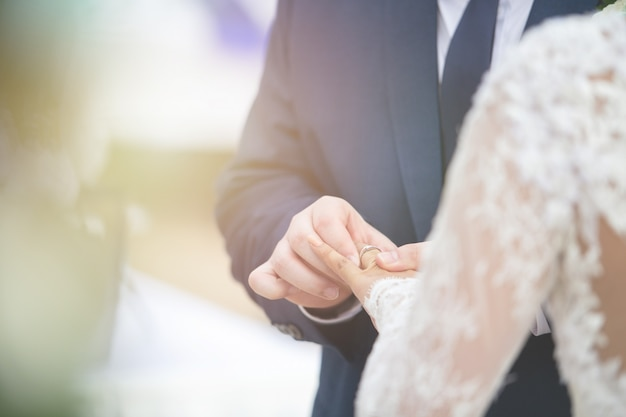 Omhoog gesloten van bruidegom gezette huwelijksdiamantring op bruidvinger in huwelijksceremonie om huwelijk te begaan.