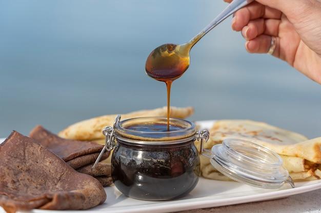 Omhoog giet de vrouwen gietende honing op smakelijke pannekoeken op de plaat ,.