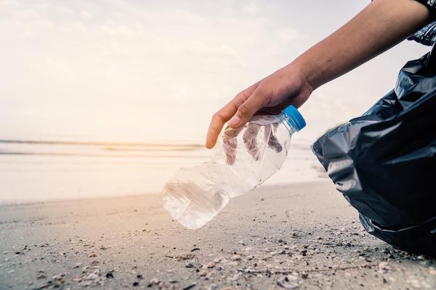 Omhoog het met de hand plukken van het plastic fles schoonmaken op het strand, vrijwilligersconcept.