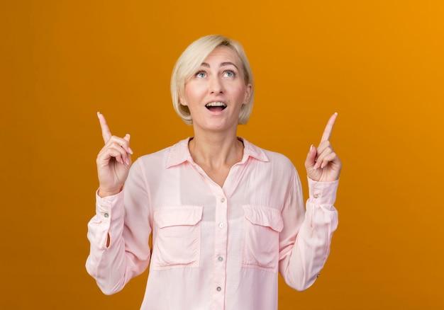 Omhoog kijken verrast jonge blonde slavische vrouw wijst naar boven