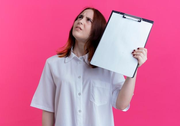 Omhoog kijken verward jong roodharig meisje met klembord geïsoleerd op roze muur