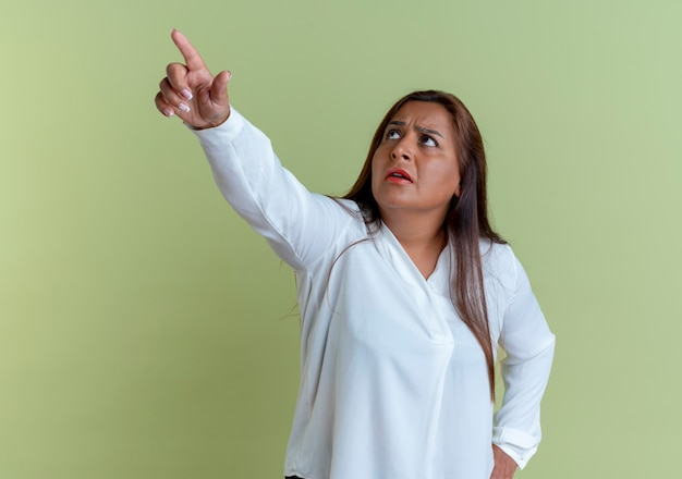 Omhoog kijken verwarde casual blanke vrouw van middelbare leeftijd wijst naar boven en hand op de heup