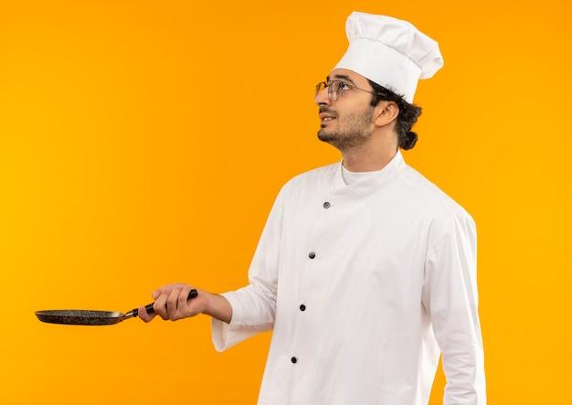 Omhoog kijkend betrokken jonge mannelijke kok die eenvormige chef-kok en glazen draagt die koekenpan houdt