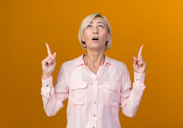 Omhoog kijkend verrast jonge blonde slavische vrouw wijst omhoog geïsoleerd op oranje muur