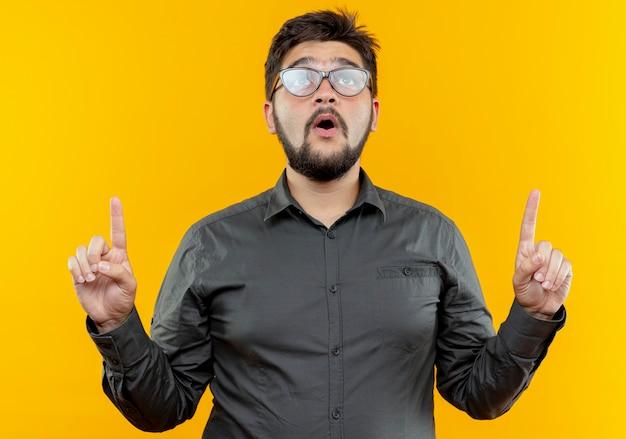 Omhoog kijkend verrast jonge zakenman die glazen draagt wijst omhoog geïsoleerd op gele muur