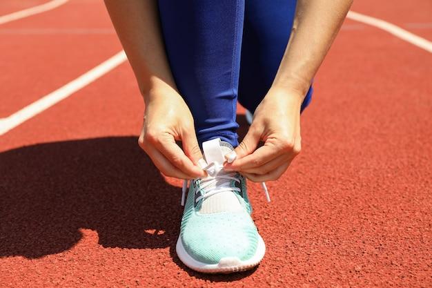 Omhoog sluiten de meisjes bindende schoenveters op rode atletische renbaan ,.