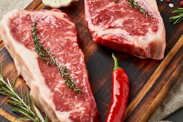 Omhoog sluiten twee groot geheel stuk van ruw rundvlees, striploin op houten scherpe raad, macro