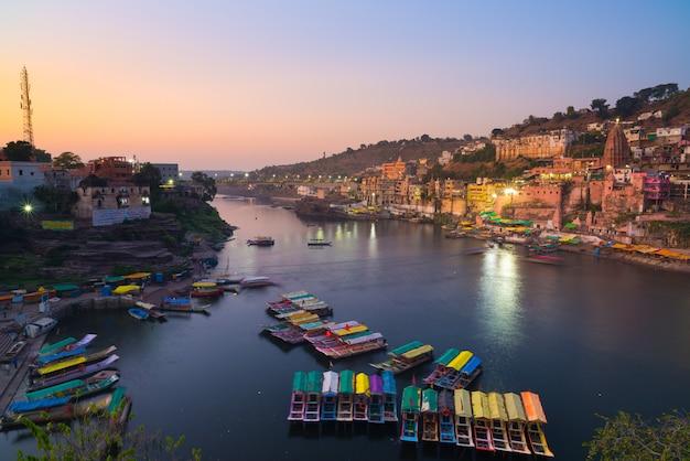 Omkareshwar stadsgezicht in de schemering, india. heilige narmada-rivier, drijvende boten. reisbestemming.