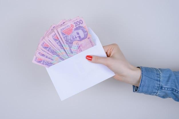 Omkopen atm jeans zaken illegale rijkdom verdienen winst ondernemer baan kopen gokken persoon mensen uitdelen concept. bijgesneden close-up foto van veel geld in witte envelop geïsoleerde muur Premium Foto