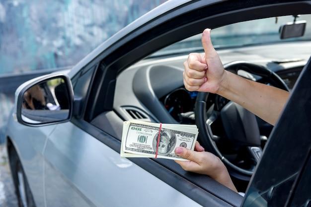 Omkoping concept. vrouwelijke handen geven dollarbundel in auto close-up