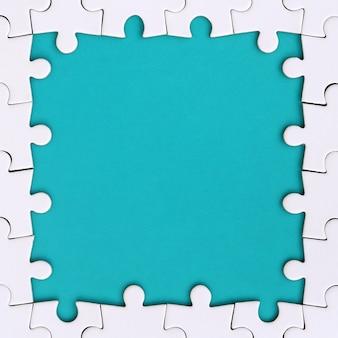 Omlijsting in de vorm van een rechthoek, gemaakt van een witte legpuzzel rond de blauwe ruimte