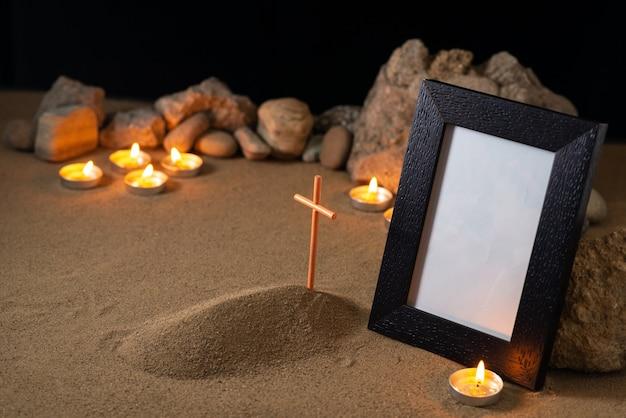 Omlijsting met stenen kaarsen en klein graf op donkere ondergrond