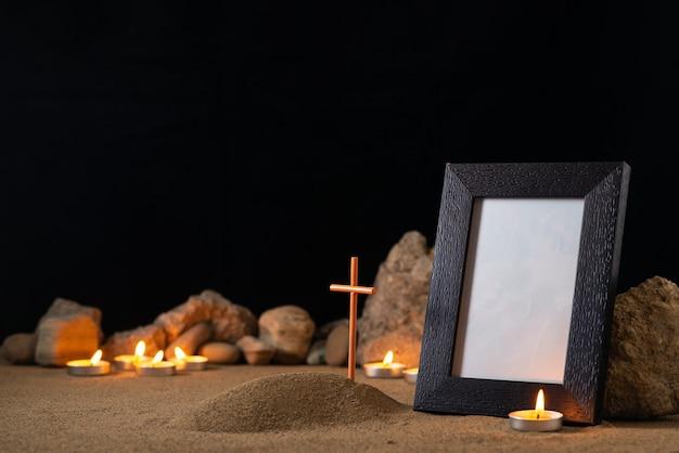 Omlijsting met stenen kaarsen en klein graf op zand donker oppervlak