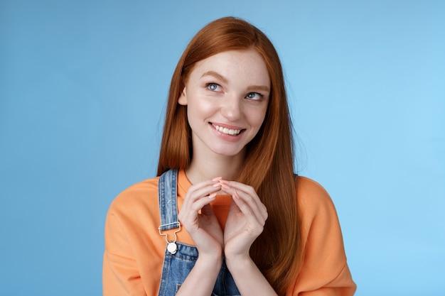 Omslachtig lastig slim mooi roodharige vriendin hebben kwaad plan grijnzend mysterieus kijken linkerbovenhoek twiddles vingers denken uitstekend plan glimlachen opgetogen staan blauwe achtergrond