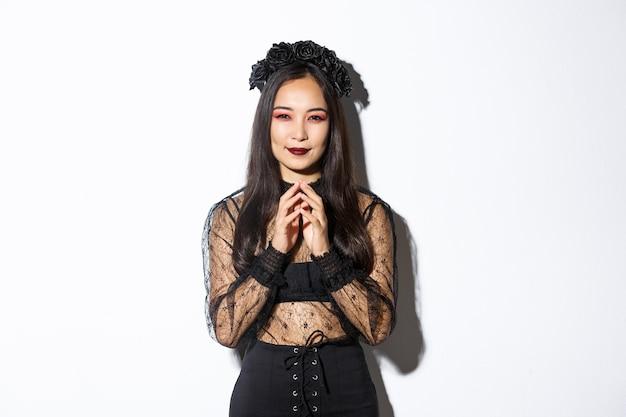 Omslachtige jonge aziatische vrouw in gotische kanten jurk glimlachend tevreden en torenvingers. heks bereidt een kwaadaardig plan voor, lacht sluw en kijkt naar de camera. halloween concept.