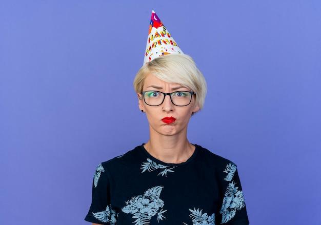 Onaangenaam jong blond feestmeisje die een bril en een verjaardagspet dragen die camera bekijkt die op purpere achtergrond wordt geïsoleerd