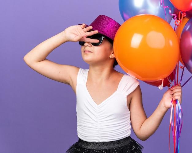 Onaangenaam jong kaukasisch meisje in zonnebril met violette feestmuts die heliumballonnen vasthoudt en hand voor gezicht houdt geïsoleerd op paarse muur met kopieerruimte