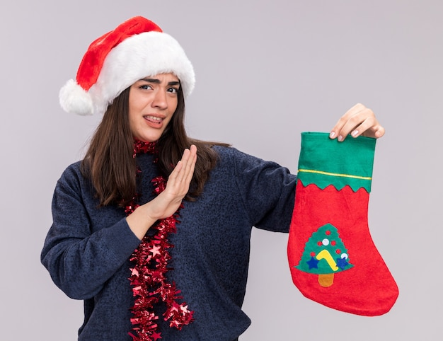 Onaangenaam jong kaukasisch meisje met kerstmuts en slinger om de nek houdt kerstsok geïsoleerd op een witte muur met kopieerruimte