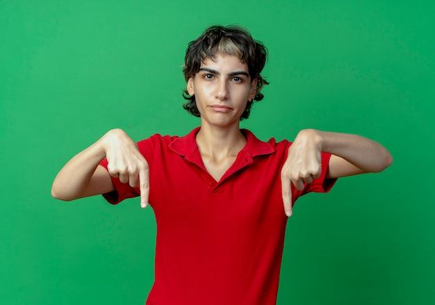 Onaangenaam jong kaukasisch meisje met pixiekapsel dat naar beneden wijst geïsoleerd op groene achtergrond