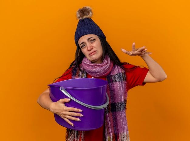 Onaangenaam jong kaukasisch ziek meisje dat de wintermuts en sjaal draagt die plastic emmer met misselijkheid houdt die hand in lucht houdt die op oranje muur met exemplaarruimte wordt geïsoleerd