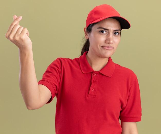 Onaangenaam jong leveringsmeisje die eenvormig met glb dragen die uiteindegebaar tonen dat op olijfgroene muur wordt geïsoleerd