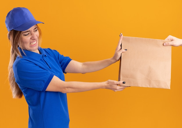Onaangenaam jong mooi bezorgmeisje in uniform geeft papieren pakket aan iemand op oranje