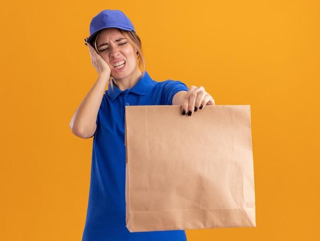Onaangenaam jong mooi bezorgmeisje in uniform legt hand op gezicht en houdt papieren pakket op oranje