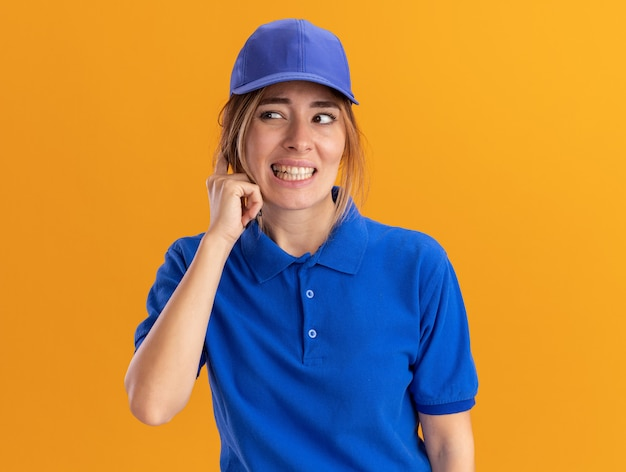 Onaangenaam jong mooi bezorgmeisje in uniform sluit oor met vinger en kijkt naar de zijkant op oranje