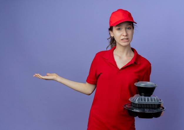 Onaangenaam jong mooi leveringsmeisje die rood uniform en glb dragen die voedselcontainers houden en lege hand tonen die op purpere achtergrond met exemplaarruimte wordt geïsoleerd