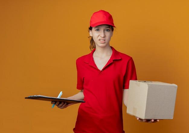 Onaangenaam jong mooi leveringsmeisje in rood uniform en glb met klembordpen en kartondoos die op oranje achtergrond wordt geïsoleerd
